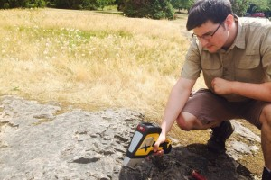 Geologist in the field testing rock with a DELTA Handheld XRF Analyzer